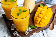 Refreshing And Healthy Mango Smoothie In A Glass With Mango On White Wooden Background.