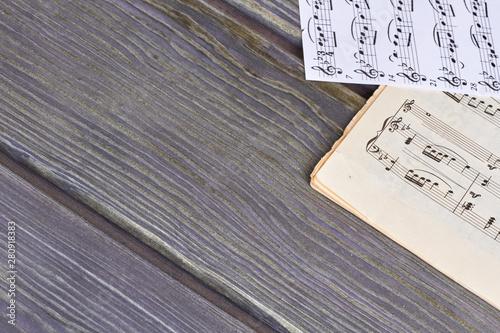 Obraz na plátne Sheets of musical notes on wooden background