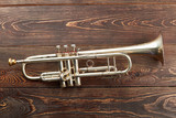 Trumpet on brown wooden background. Rusty trumpet on textured wooden surface. Classical music wind instrument.