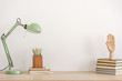 canvas print picture - Pastel mint colored lamp on wooden desk with books, copy space on empty white wall