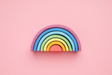 Fototapeta Rainbow - Colorful Waldorf wooden rainbow in a montessori teaching pedagogy on pink background