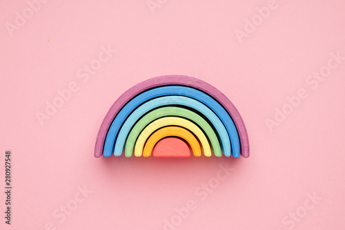 Colorful Waldorf wooden rainbow in a montessori teaching pedagogy on pink background