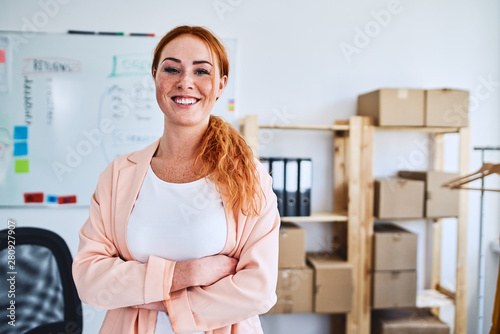 Young businesswoman standing proudly with arms crossed and smiling at camera in her startup office