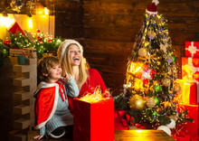 Mom And Kid Play Together Christmas Eve. Family Holiday. Happy Family. My Dear Baby Santa. Mother And Little Child Boy Adorable Friendly Family Having Fun. Family Having Fun At Home Christmas Tree