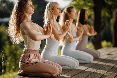 Obraz Four young girls are practising yoga sitting  on the wooden podium in the garden with folded hands near the chest - fototapety do salonu