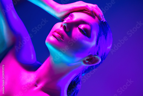 Fashion model woman in colorful bright neon lights posing in studio. Portrait of beautiful sexy dancing girl in UV. Art design colorful makeup