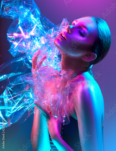 Foto op Canvas Beauty Fashion model woman in colorful bright neon lights posing in studio through transparent film. Portrait of beautiful sexy girl in UV. Art design colorful makeup