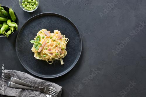 Fotografia  Pasta tagliatelle with cream, peas and bacon on black background