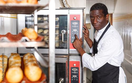 Foto op Plexiglas Bakkerij Baker programming professional oven at bakery