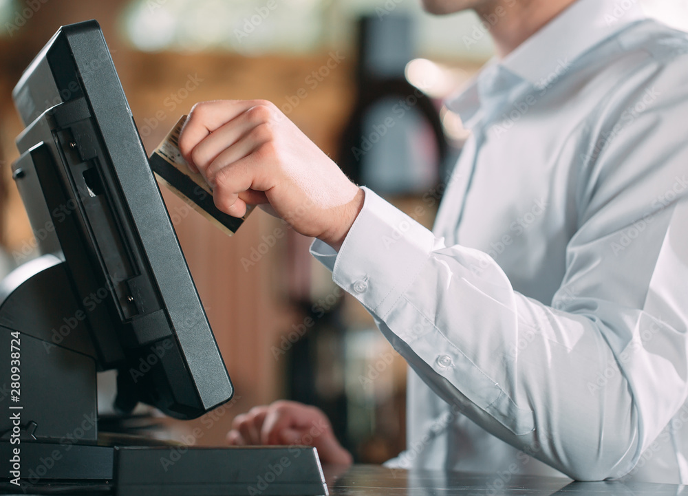 Fototapeta small business, people and service concept - happy man or waiter in apron at counter with cashbox working at bar or coffee shop.