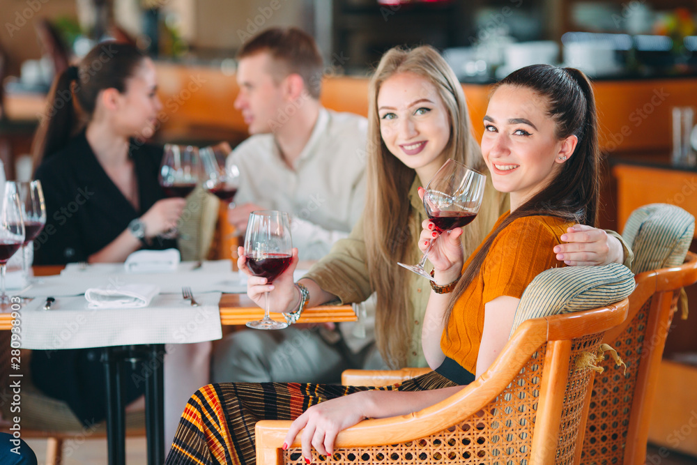 Fototapety, obrazy: Friends have fun drinking wine, talking and smiling in the restaurant.