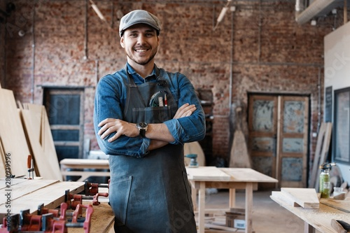 Obraz Successful handsome businessman with stylish cap work in carpentry - fototapety do salonu