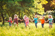 canvas print picture - Large group of kids, friends boys and girls running in the park on sunny summer day in casual clothes .
