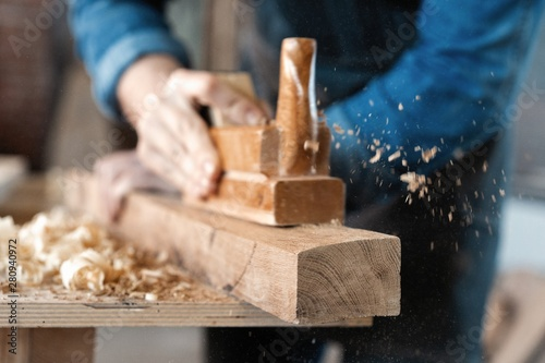 Canvas Print carpenter working with plane on wooden background.