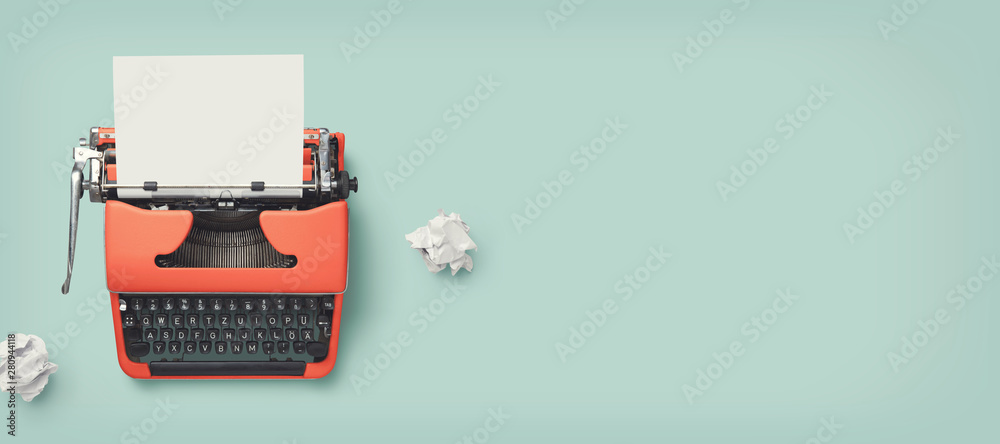 retro banner with red vintage typewriter with a blank sheet of paper and paper balls, top view, copyspace