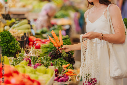 Young Woman puts fruits and vegetables in cotton produce bag at food market. Reusable eco bag for shopping. Zero waste concept.