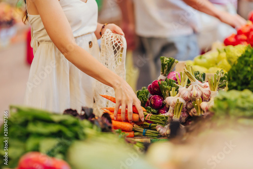 Female hands puts fruits and vegetables in cotton produce bag at food market Tableau sur Toile