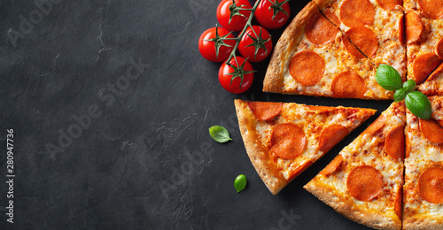 Cadres-photo bureau Pizzeria Tasty pepperoni pizza and cooking ingredients tomatoes basil on black concrete background. Top view of hot pepperoni pizza. With copy space for text. Flat lay. Banner