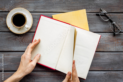 Fotografija  workplace with book in hands for reading, glasses, coffee on wooden background f