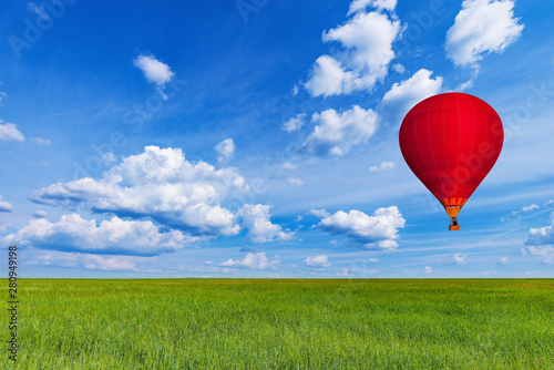 Poster Montgolfière / Dirigeable Red hot air balloon above the field with rye at day time.