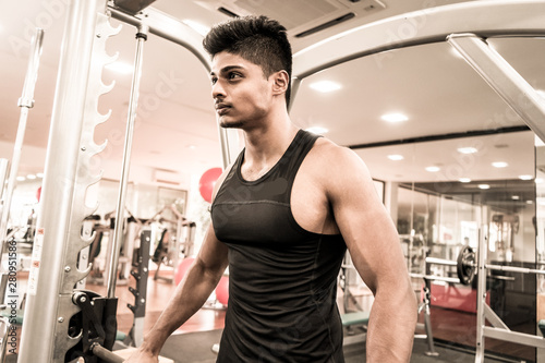 training shot of a young man in the gym, dumbbell, shrugs Canvas-taulu