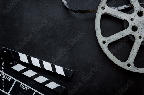 Photo  Movie premiere concept with clapperboard, film type on black background top view