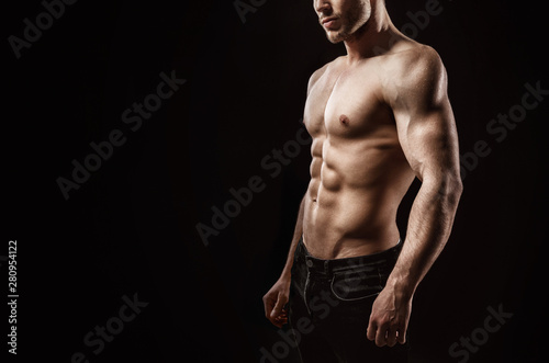 Muscular model sports young man on dark background Tablou Canvas