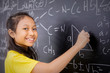 Happy female student writes mathematical formula
