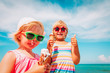 happy cute little girls eating ice cream on beach