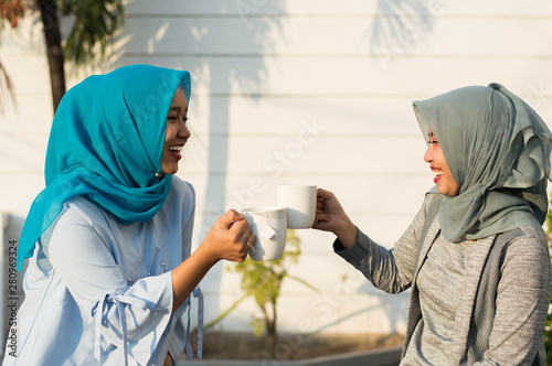 Fototapeta  close up happy shot two hijab women drinking tea in front of the house and smili