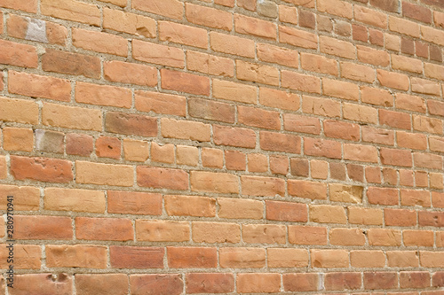 Antique brick wall background with light brown coloring and eroded appearance