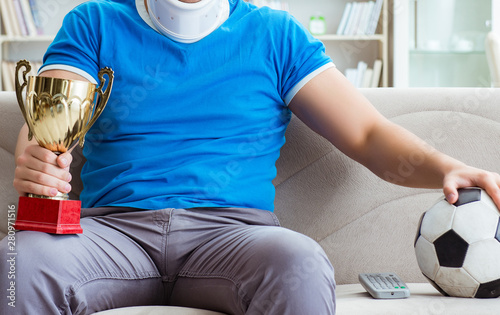 Man with neck injury watching football soccer at home Canvas-taulu