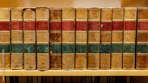 Obraz Antique leather cover books on wooden bookshelf in university public library. Reading philosophy or history studying. Education research and self learning concepts - fototapety do salonu