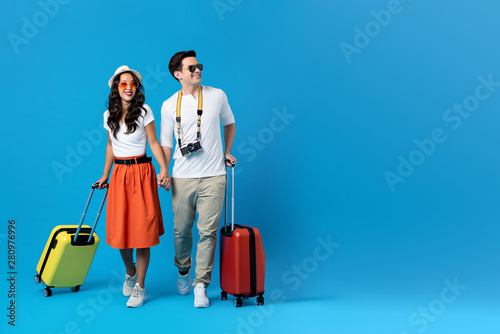 Young couple going for holidays with colorful suitcases Fotobehang
