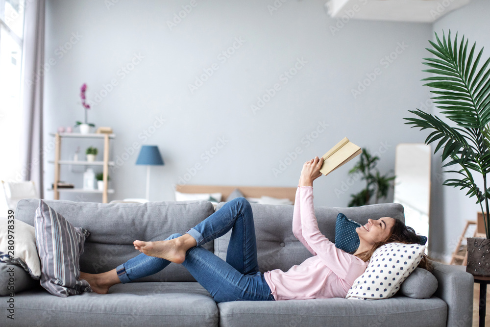 Fototapety, obrazy: Beautiful smiling woman reading a book and lying on the sofa in the living room.
