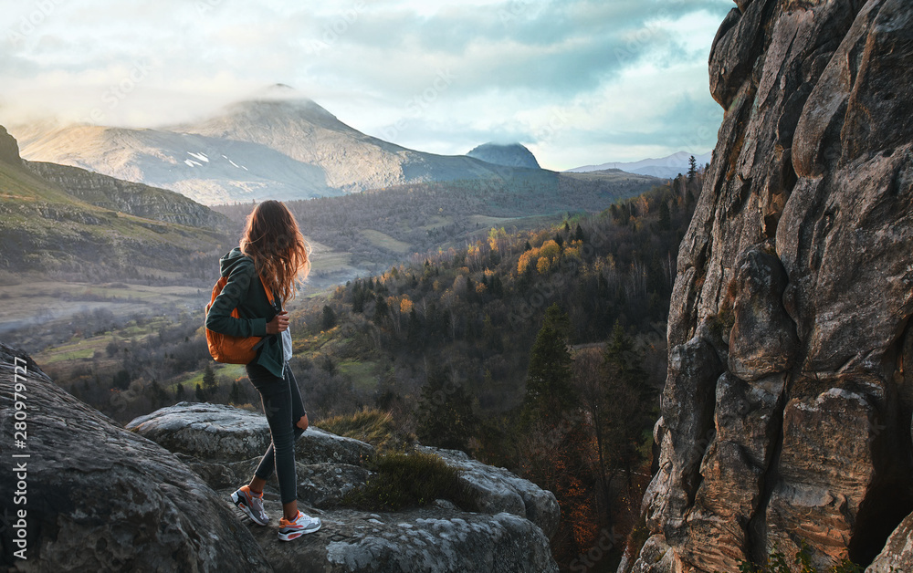 Fototapety, obrazy: woman standing on edge of cliff against background of sunrise
