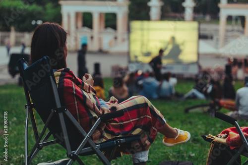 Fotografija woman eating chips sitting in camp-chair looking movie in open air cinema