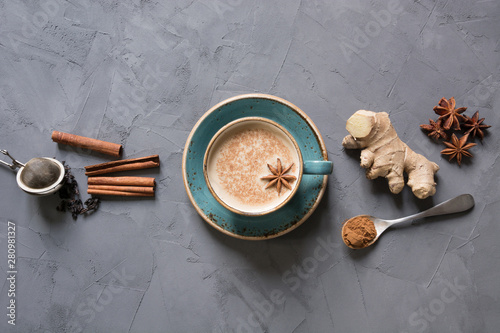 Fototapeta Masala Indian tea in cup with spices on grey concrete table. Top view. obraz
