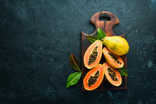 Fresh Papaya On A Black Stone Background. Tropical Fruits. Top View. Free Space For Text.