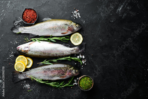 Raw fish trout with vegetables on a black stone background Fototapeta