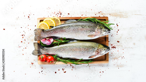 Fotografia Raw fish with vegetables on a white wooden background