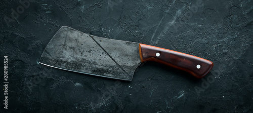 Fotografía Kitchen old knife on a black stone table