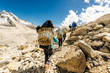 canvas print picture - Porter and Sherpa walking with big bag baggage luggage in Himalaya Mountains in Nepal.