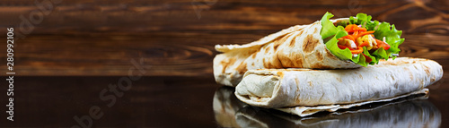 Delicious shawarma sandwich on wooden background. Banner.