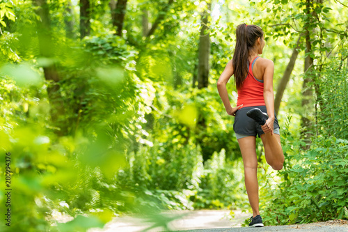 Leinwand Poster Fit stretch woman stretching quad leg muscle standing getting ready to run jogging outside in summer nature forest park green trees background
