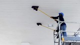 Selective focus of 2 workers on scaffolding using flat wet mops to cleaning white ceiling of petrol station, occupation concept, low angle view copy space