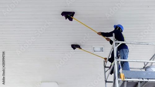 Fotografie, Obraz  Selective focus of 2 workers on scaffolding using flat wet mops to cleaning whit