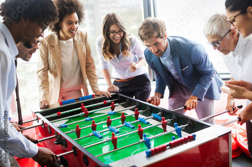 Obraz Employees playing table soccer indoor game in the office during break time - fototapety do salonu