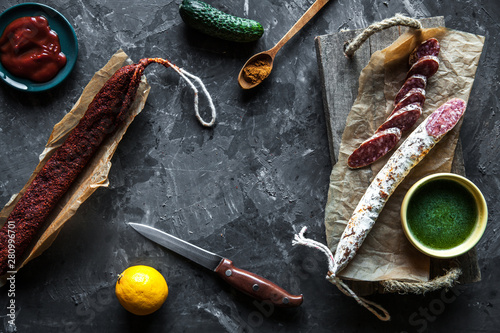 Valokuvatapetti Sausage on a dark background with elements of cooking