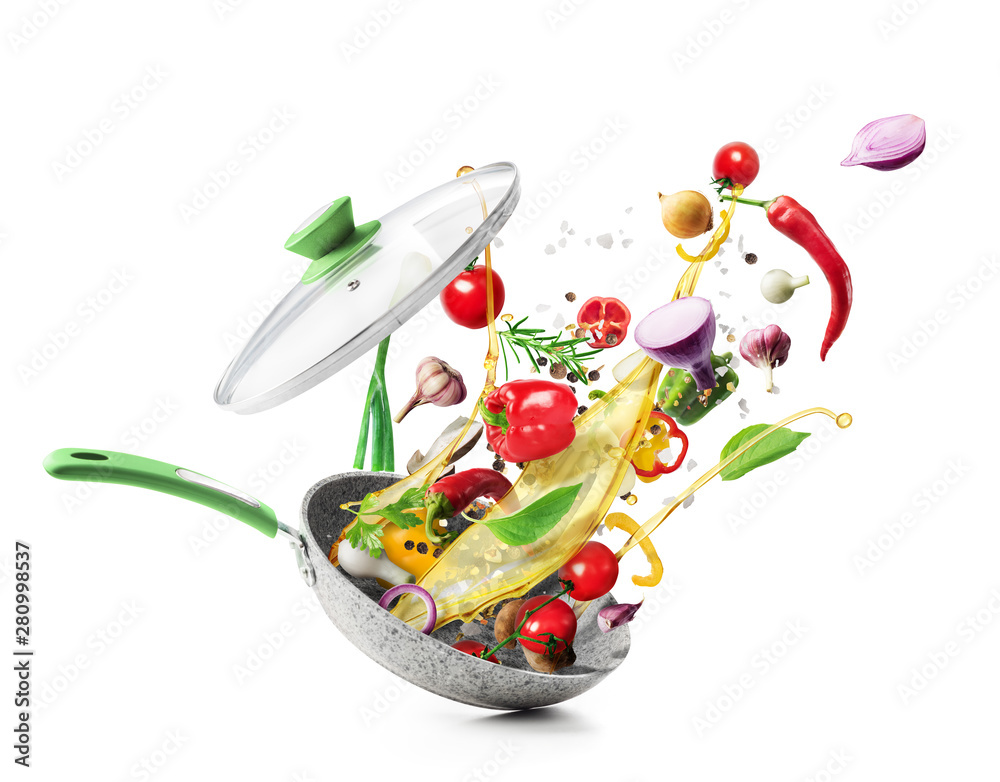 Fototapeta Cooking concept. Vegetables are flying out of the pan isolated on white background. Healthy food.